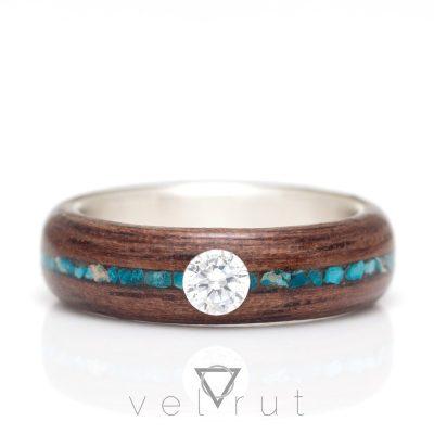 Nişan veya evlenme teklifi için tercih edilen, gümüş astar ve ortalı ince koyu firuze/turkuaz dizili ve tektaşlı ceviz sarma ahşap yüzük.